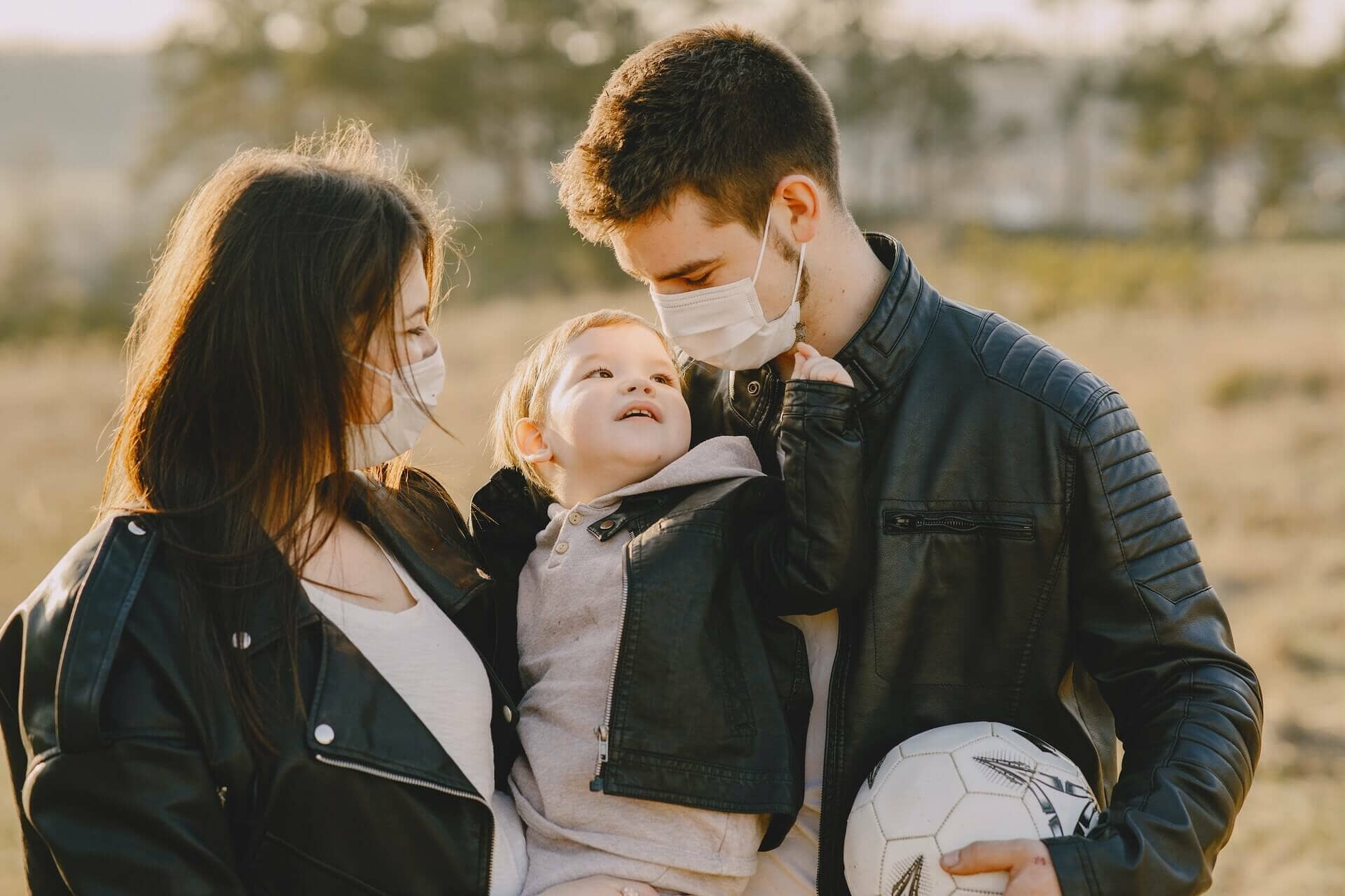 Young parents with toddler wearing masks for COVID-19 protection