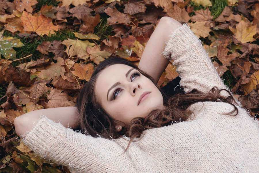 photo of woman lying on the ground looking at the sky, pondering whether she might have the breast cancer gene